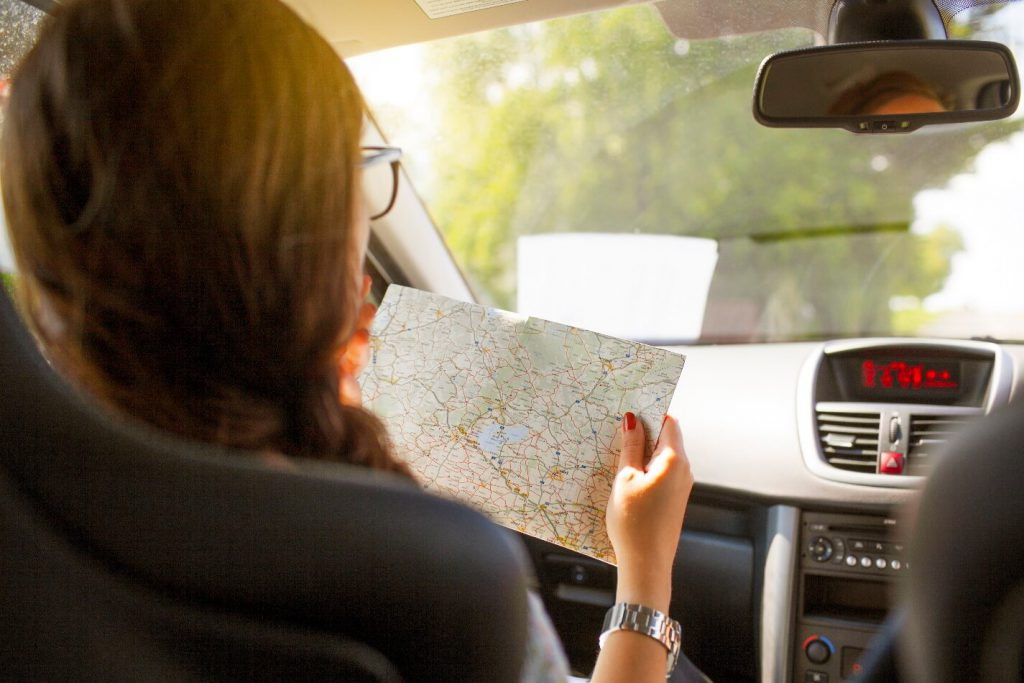 woman with paper map in car